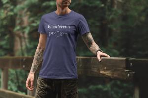 Man wearing Emottercon Unisex T-shirt in Heather Midnight Navy in the woods.